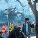 Garth Martens reads to Robert Wyland orca mural.